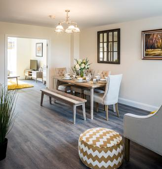 The living room of a showhouse in Alderlie connects to the dining area