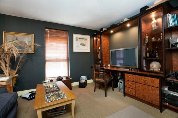 The study is stylishly decorated with dark walls and a fitted bookcase