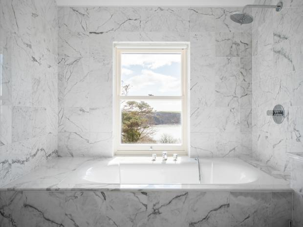 The bathroom with a picture window overlooking the water