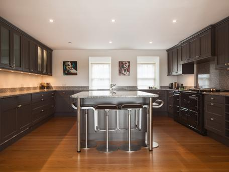 The dark-grey kitchen cabinets are offset by pale walls in Hartt House