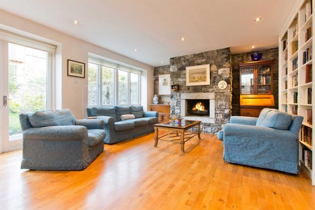 The living room features a fireplace in an exposed stone wall