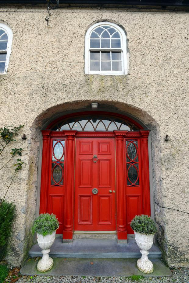 The front door is situated in one of the arched former-carriage entrances