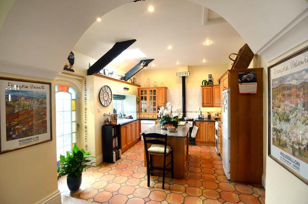 The kitchen has a country feel to it with beech cabinets, centre island and terracotta floor