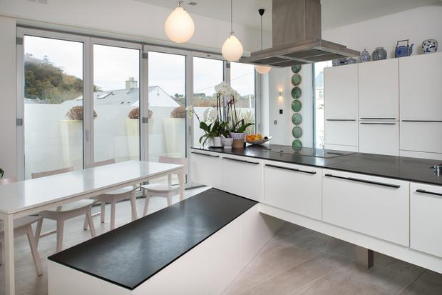 In the kitchen, which has doors opening onto the courtyard, Clifden and Orna opted for white units in the kitchen with an unusual L-shaped, two-tier island; the lower tier doubles as storage