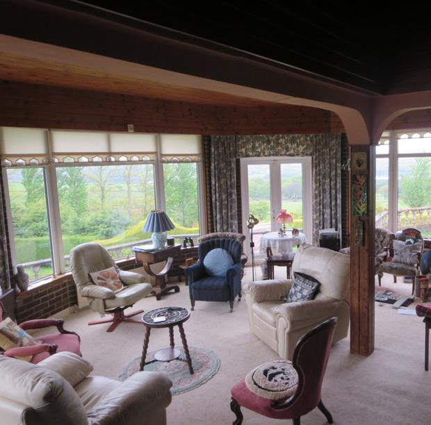 Split-level lounge with bay windows and solid-fuel stove