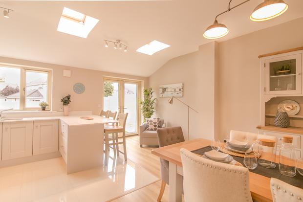 The kitchen/dining space is flooded with light from skylights in the vaulted ceiling