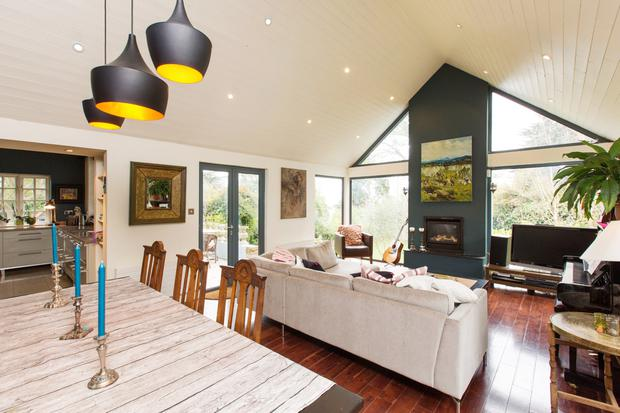 The open-plan sitting/dining room with French doors opening out onto the deck and terrace
