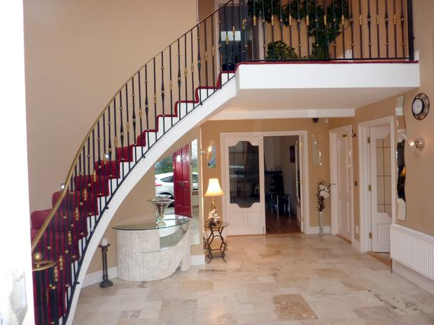 Entrance hall with an Italian tiled floor and curved staircase