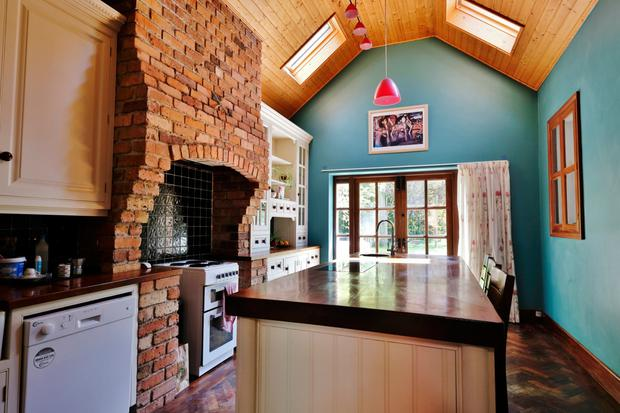 The kitchen has a red-brick chimney for a range or Aga