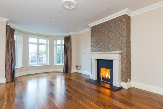 The bay-windowed living room with a walnut floor and feature fireplace