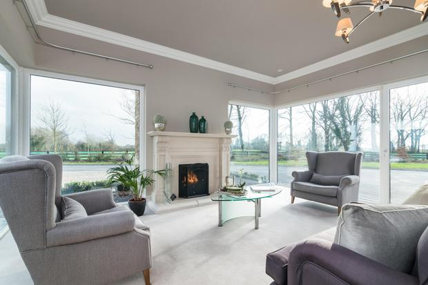 The living room features floor-to-ceiling windows