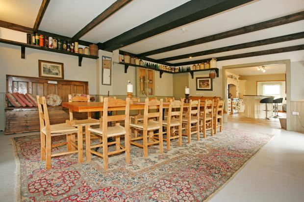 The large dining room has a beamed ceiling and doors to the garden