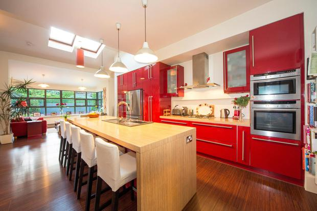 The kitchen is fitted with high-gloss red cabinets
