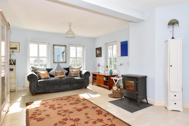The living/dining room has a wood-burning stove and access to the rear garden