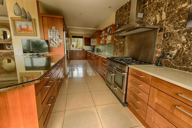 The kitchen is fitted with walnut cabinets and breakfast bar