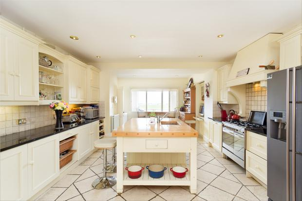 The large open-plan kitchen features an island unit and handcrafted solid wood units