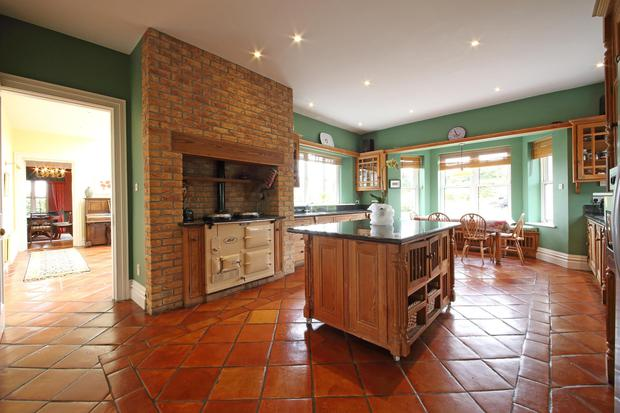The fitted kitchen has handmade floor tiles and an Aga
