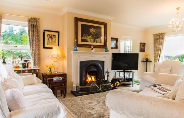 The double aspect living room has an open fireplace and views out to Kenmare Bay