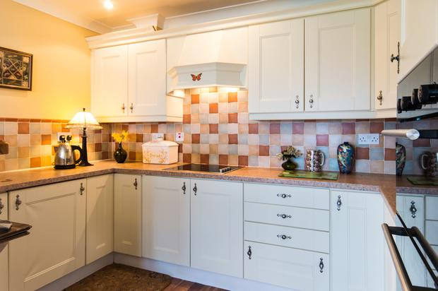 The kitchen is fitted with white units