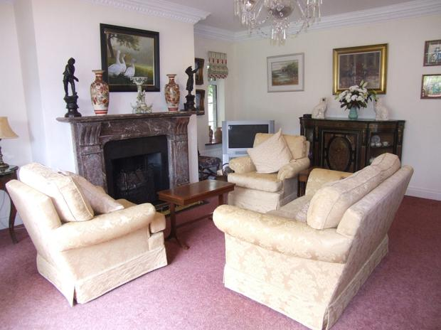 A marble fireplace is the focal point of one of the reception rooms