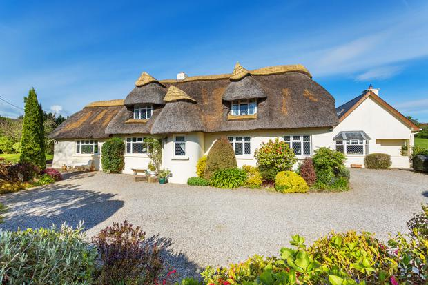 The traditional-style English thatched cottage was built in the 1950s