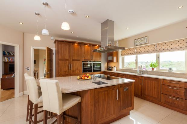 The walnut-fitted kitchen has a centre island with breakfast bar