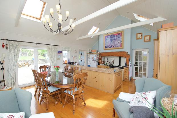 The open-plan kitchen and dining room has a vaulted ceiling, an Aga and doors to the terrace