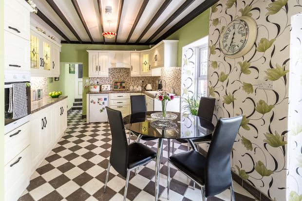 The eat-in kitchen with a beamed ceiling and tiled floor