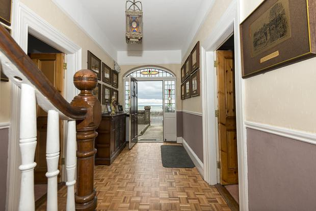 The hallway and front door, opening on to views of the water beyond