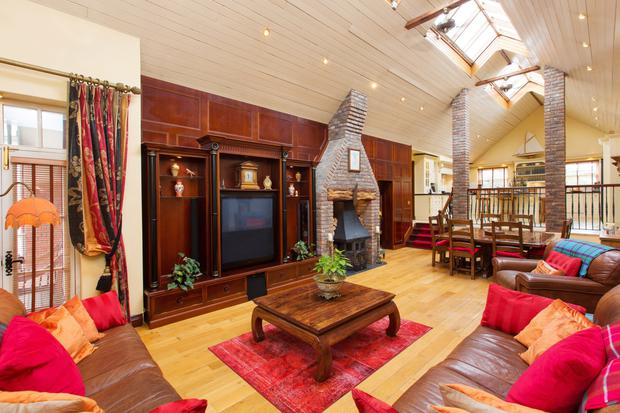 The living room which adjoins the kitchen and benefits from plenty of natural light with vaulted ceilings and roof windows