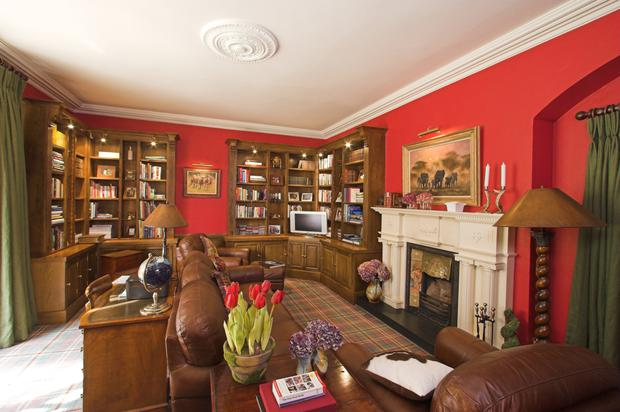 The library room with its bespoke in-built shelving and cupboards and a distinctive white carved marble chimney piece