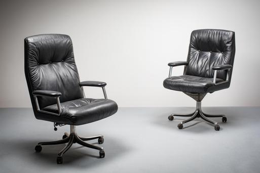 A pair of black leather swivel chairs by Osvaldo Borsani