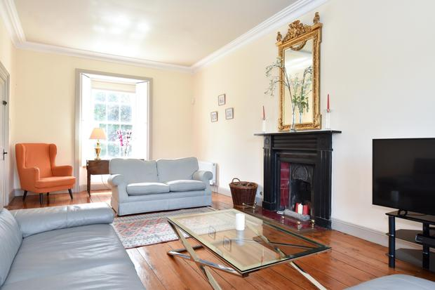 The sitting room has a shuttered sash window and a fireplace