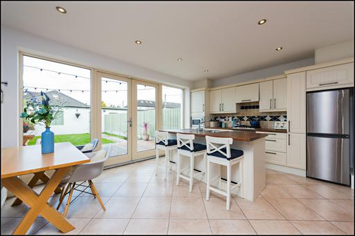 The open-plan kitchen, dining and family room has doors to the garden