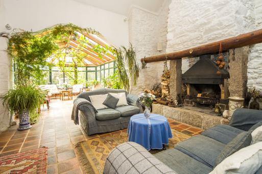The family room has a huge old stone fireplace and a terracotta-tiled floor, and opens directly into a sunroom