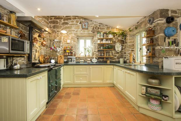 The kitchen with a terracotta floor and green Aga
