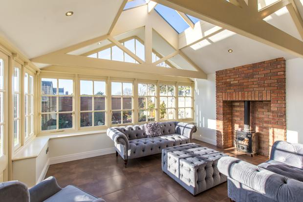 The bright sunroom has a wood-burning stove