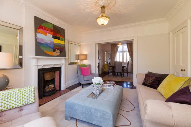 The living room links through double doors to the dining room, both with original fireplaces