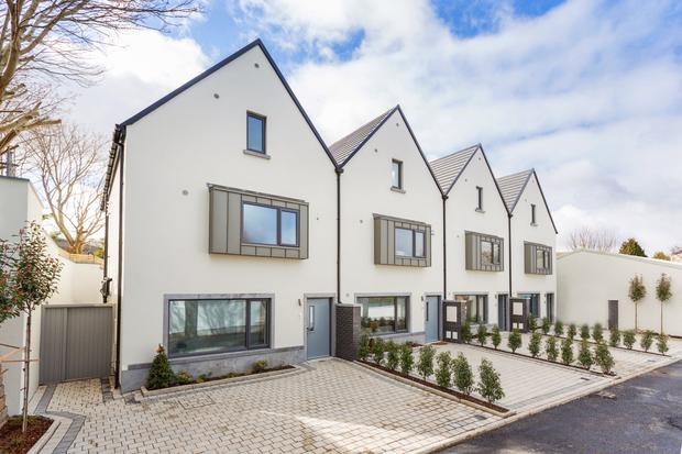 The four houses in the enclave at Edmondstown Close have zinc boy-bay windows to the facade, triple-glazed Alu-clad windows and grey front doors