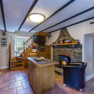 The kitchen has a beamed ceiling and terracotta-tiled floor