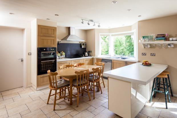 The kitchen is fitted with wooden units and a breakfast bar