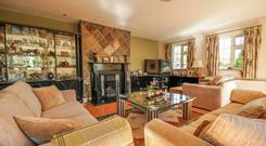 The dual-aspect sitting room has a corner bar and a fireplace.