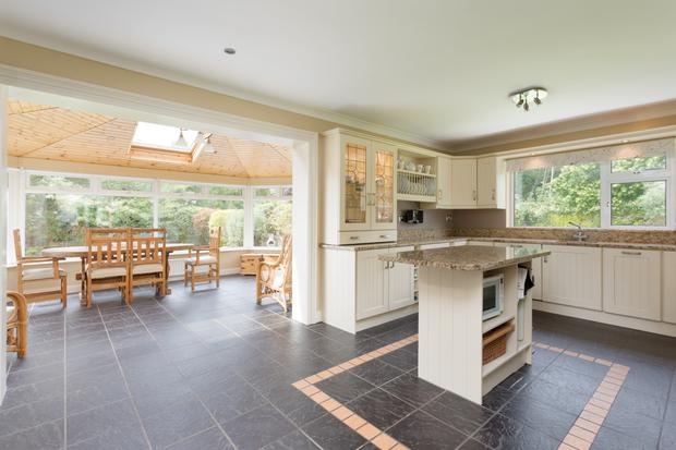 The kitchen opens via an archway to the sunroom