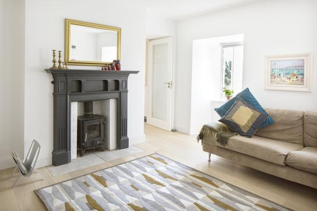 The sitting room is still the original size, but Goretti augmented the comfort level by installing the stove. The rug is from Avoca