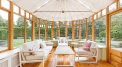 The Irish Conservatories sunroom in cedarwood has an antique oak floor and new canvas ceiling blinds, double doors lead out to the south-facing patio