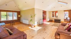 The ground floor includes a sunroom (pictured), three reception rooms and a kitchen