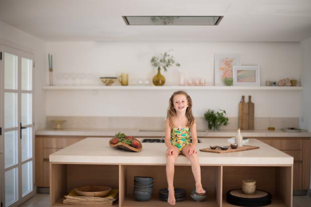 Eden in the kitchen. The stone worktop is from Binissalem, and the ceramics on the worktop are by Dora Good from the Oma Project in Deia