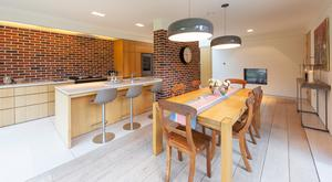 The modern and bright kitchen and dining area incorporates the same style of red-brick used in the pram porch to provide a defining feature for a wholly contemporary interior