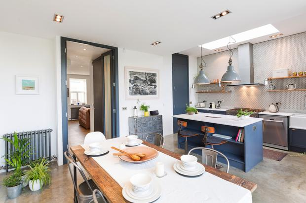 The new kitchen/living area at 176 Foxrock Close which features industrial lighting and vintage metal cabinets
