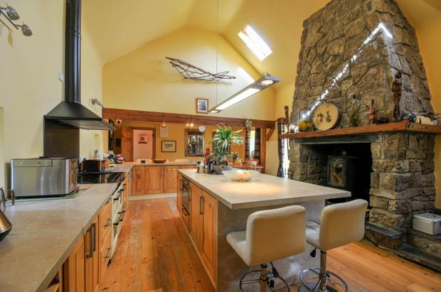 The kitchen with double-height ceiling and original fireplace